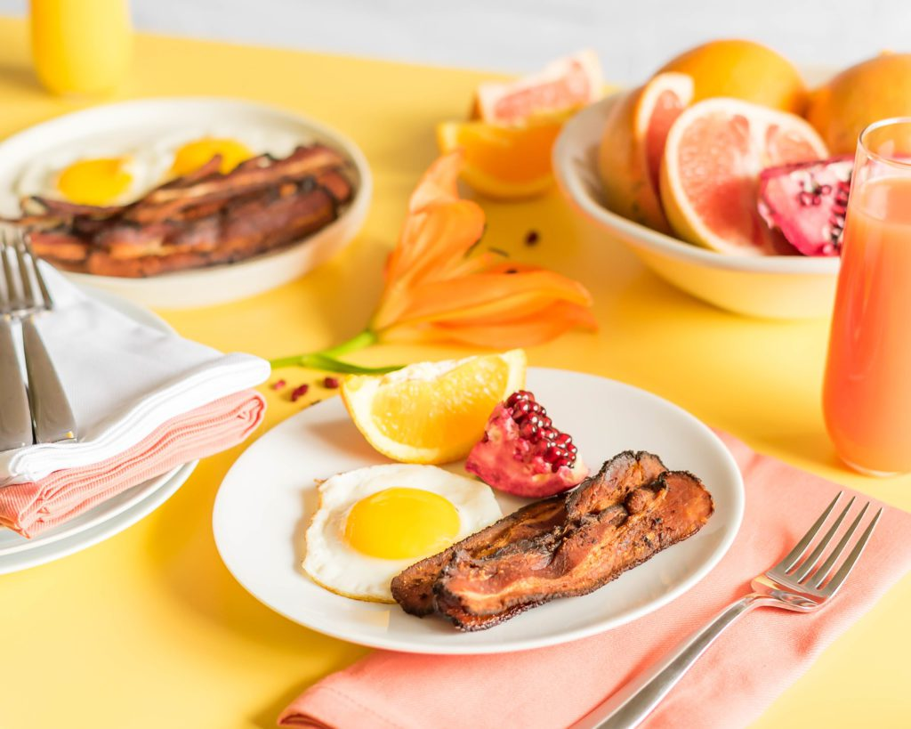 Sous Vide Bacon next to eggs and fruit